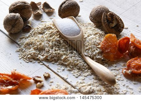 Ingredients for dietary recipe oatmeal cookies: oatmeal, erythritol (erythritol), dried fruits, nuts. Om white rustic wooden table.