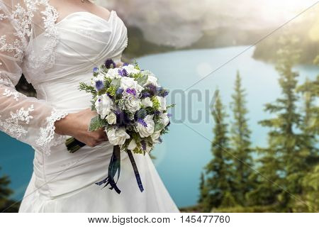 Bride in white dress with wedding bouquet by a beautiful lake