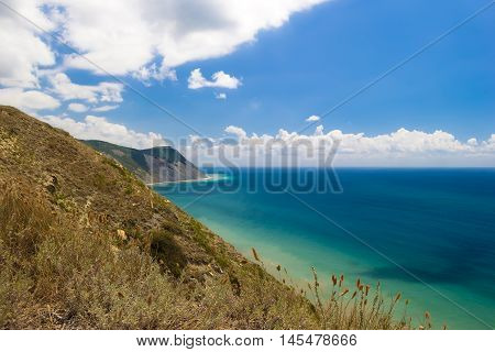 Beautiful mountain view on Black sea beach from the top of hilll. Azure water, blue cloudy sky. Hill with dry grass in foreground.