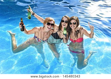 group of three young attractive happy girl friends having bath in swimming pool together having fun enjoying drinking beer bottle playing at summer vacation resort smiling in women holiday concept