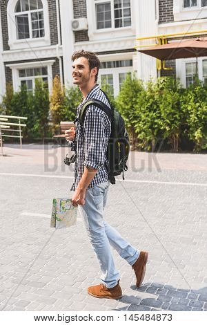 Joyful young man is making touristic journey in city. He is looking around and smiling. Man is holding map, camera and backpack