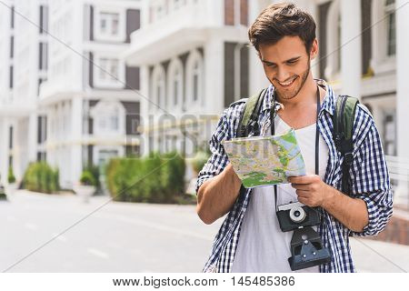 Happy male tourist is looking for location. He is standing on street and holding map. Guy is laughing