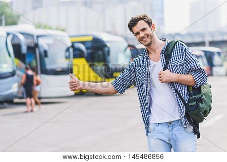 Hitch-hiking. Happy male tourist is catching transport near bus station. He is looking forward and smiling