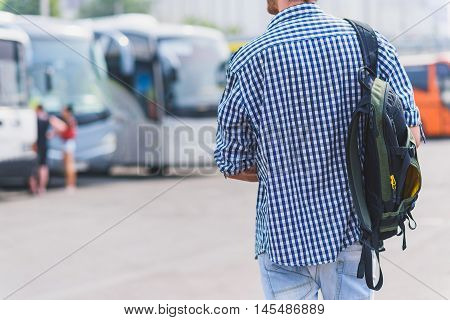 Young man is searching his bus on station. He is standing and holding backpack. Focus on his back