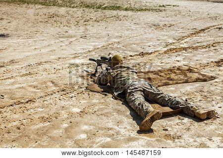 Young male sniper in camouflage with gun in the desert poster