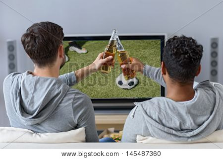 Two young men are watching football with concentration. They are sitting on sofa and clinking bottles of beer. Focus on their back