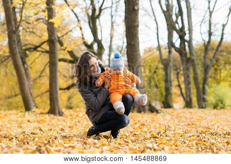 Mother and her toddler son playing in the park. Autumn nature background. Love and family concept.