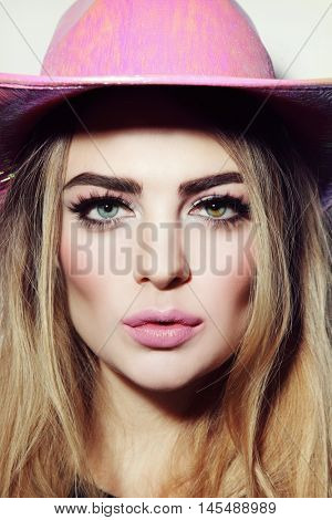 Vintage style portrait of young beautiful blonde girl with stylish make-up in party pink cowboy hat