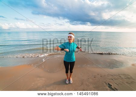 Young Sporty Girl Doing Workout On Beach At Sunrise In Morning