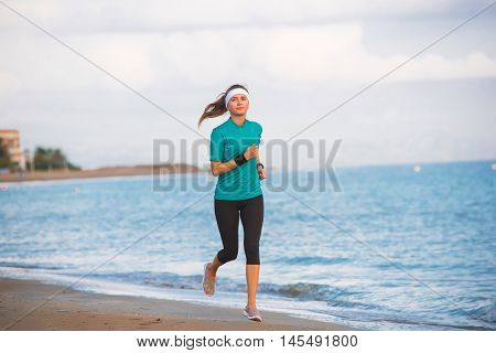 Young Fit Girl Running On Beach At Sunrise In Morning