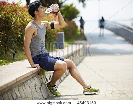 young handsome asian jogger taking a break and drinking water from a bottle side view