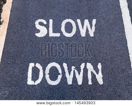 Close up of 'SLOW DOWN' sign marking on bike lane for warning the drivers and cyclist to reduce speed.