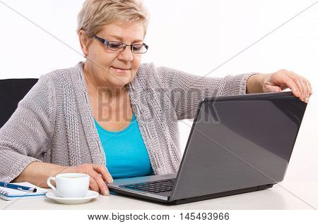 Elderly Senior Woman Closing Laptop On Table At Home