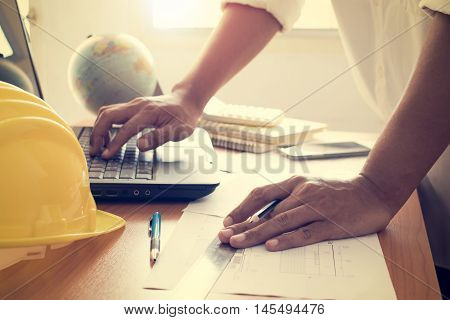 Hands Of Architect Working On Laptop With Construction Plan