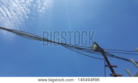 black binded wire and spot light with blue sky background on sunny day