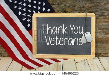 Thank You to veterans sign on black chalkboard with military dog tags on American flag