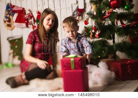 Sister And Little Brother Unpacking Presents In Front Of Christmas Tree