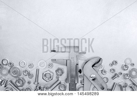 Vernier Caliper And Adjustable Wrench With Bolts And Nuts On Scratched Metal