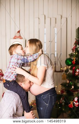 Young Pregnant Mother, Father And Small Son Celebrating Christmas At Home