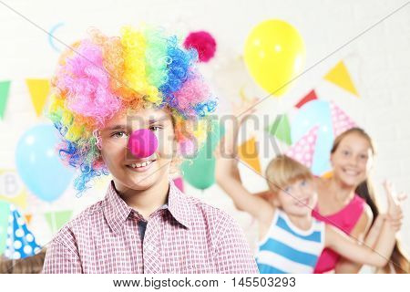Little boy clown and girls having fun at birthday party