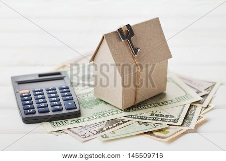 Model of cardboard house with key, calculator, notebook and cash dollars. House building, loan and real estate. Cost of public utilities, insurance, rent or buying a new home concept.