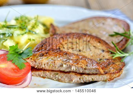 Bavarian food: Fried slices of sausage with pieces of pig spleen (so called 'Milzwurst') served with potato salad
