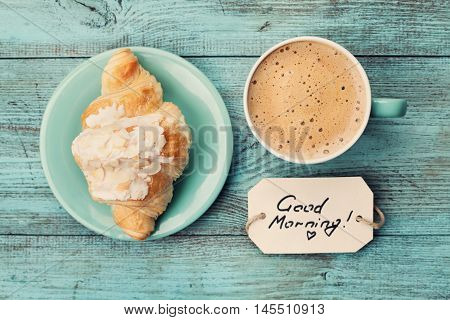 Coffee mug with croissant and notes good morning on turquoise rustic table from above, cozy and tasty breakfast, vintage toned.