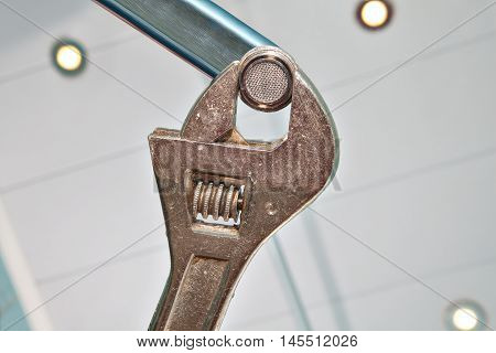 Fixing a Faucet Aerator using an adjustable wrench plumber hands handyman close-up.