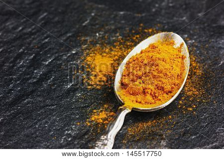 Ground turmeric or curcuma in silver vintage spoon on black stone surface. Copy space for text.