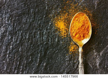 Ground turmeric in silver vintage spoon on black stone surface. Copy space for text.