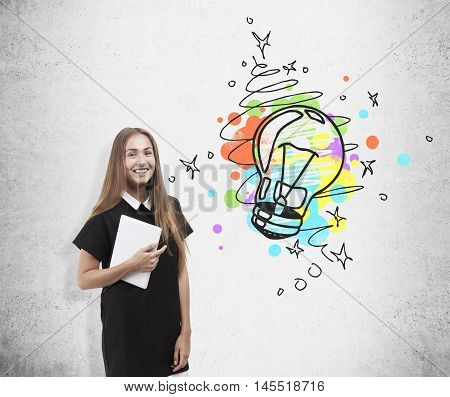 Cheerful business lady and light bulb sketch on concrete wall. Concept of new original idea in marketing