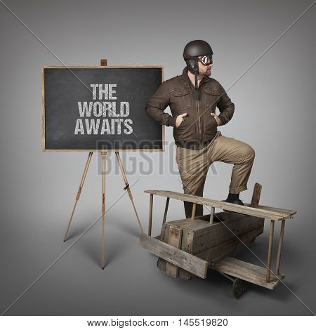 The world awaits text on  blackboard with businessman and wooden plane