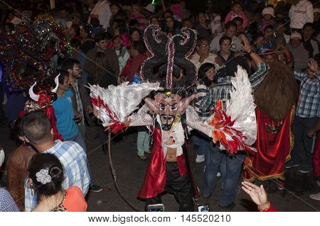 Píllaro ECUADOR - FEBRUARY 6 2016: Unknown locals dressed up participating in the Diablada popular town celebrations with people dressed as devils dancing in the streets