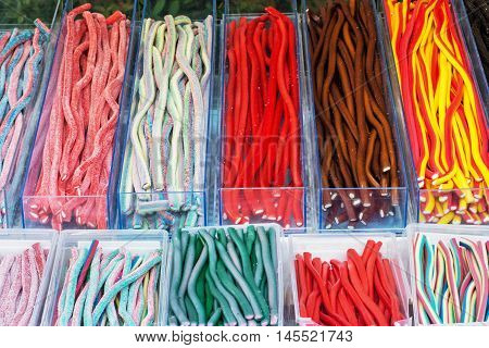 Multicolor tasty licorice candies in plastic containers. Sweet delight. Confectionery in the shop. Vibrant colors. Sweetmeats scene.