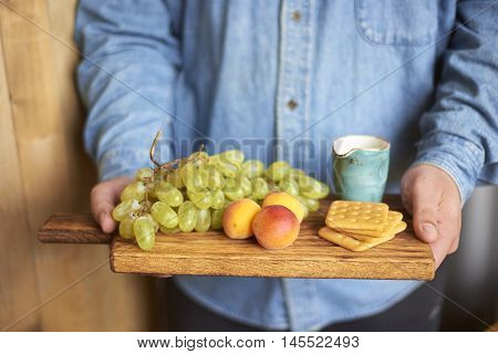 Fresh grapes and apricots with crackers on wooden board