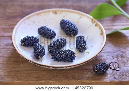 Plate wiht fresh sweet mulberry on wooden table