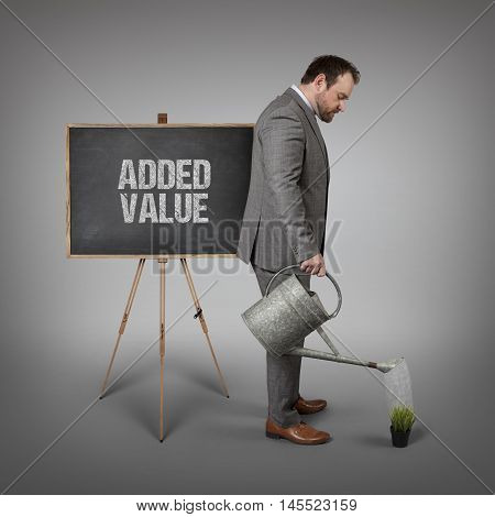 Added value text on  blackboard with businessman watering plant