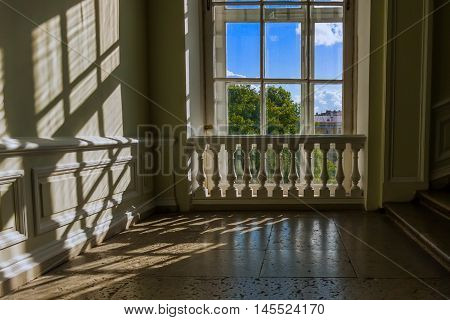 Classic white window with balustrade with sunlight on wall and green summer tree behind.