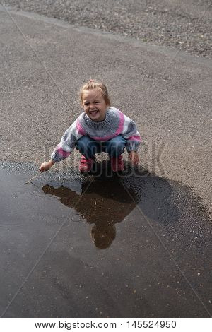 Little girl playing in a big puddle on asphalt.