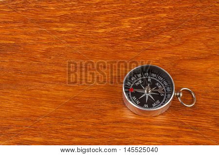Simple black compass on brown wood flat surface
