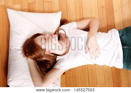 A young adult Woman sleeping on the floor.