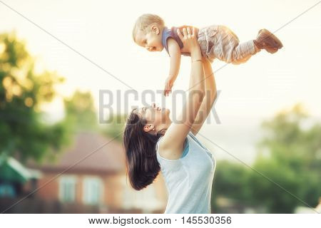 Portrait of mother and baby outdoor on the sunset. Mom and her one years old baby boy have fun on the park. Mum throws kid and child smiling and laughing