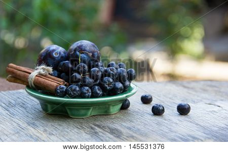 Black chokeberry (Aronia melanocarpa) and plums on wooden table. Home atmosphere. Autumn concept. Autumn harvest