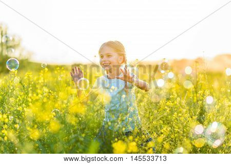 Bubbles is wonderful thing. Portrait of cute young girl laughing happily while surrounded by bubbles