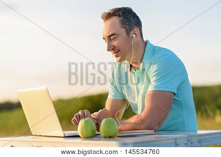 Connected while picnicking. Shot of adult man sitting at picnic table outdoors and using digital tablet with headphones