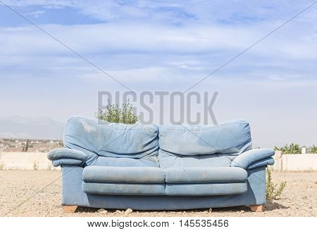 a blue sofa in the outdoors against a blue background