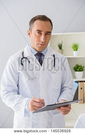 I am ready to tell your diagnosis. Portrait of mature doctor holding patient file in his hand and looking at camera