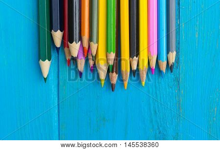 Colored pencils on a blue wooden background. Copy space