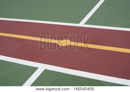 center of futsal field with green red and yellow color water flooding on a floor