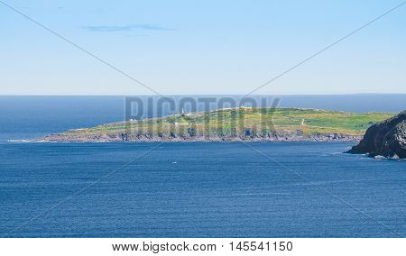 Cape Spear seen from Signal Hill.  Panoramic vista - bright, blue summer sky looking out over the Atlantic to Cape Spear from Signal Hill in St. John's Newfoundland, Canada.